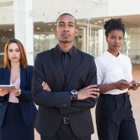 Successful business team posing in office hall. Three mix raced professionals with arms crossed standing in office hall and looking at camera. Multiethnic business team concept